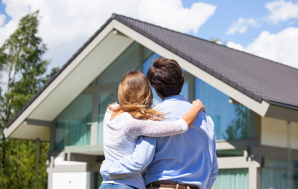 couple with arms around each other facing brand new home